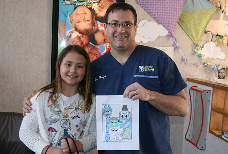Dentist posing with patient and coloring contest picture