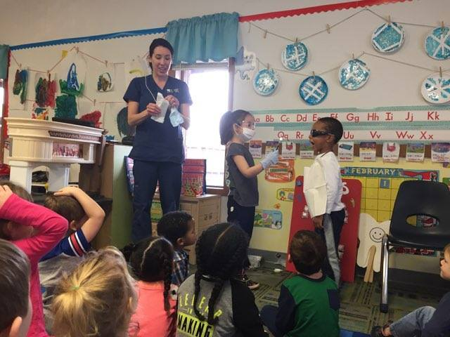 Dentist teaching kids to brush in classroom