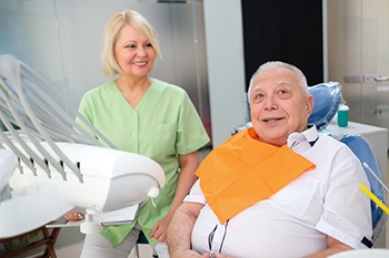 Older man consulting dentist on multiple tooth replacement in Portage.