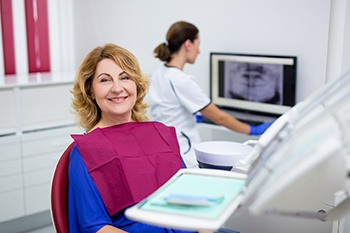 An older woman smiling at her implant consultation.