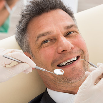 Man with healthy smile receiving dental exam