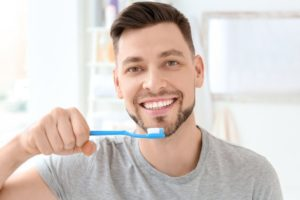 Man in grey shirt brushing his teeth