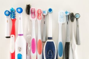 a lineup of different used toothbrushes